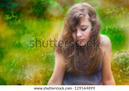 Shy teenage girl alone outside in nature - stock photo