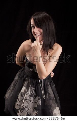 Shy woman in dark with finger in mouth - stock photo