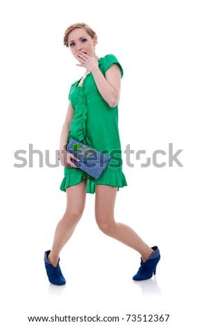 Shy woman in green with small blue purse on white - stock photo