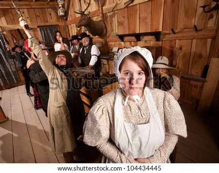 Shy woman with rowdy people in an old west saloon - stock photo
