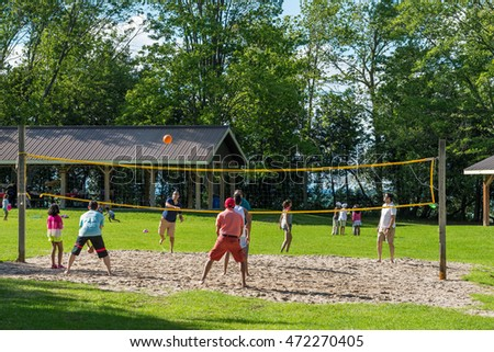 Sibbald Point Provincial Park, Ontario - August 21, 2016: Group of adults and children are playing volleyball at the Sibbald provincial park on the southern shore of Lake Simcoe in Ontario.