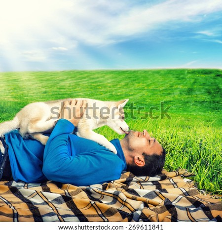 Siberian Husky. Siberian Husky dog puppy playing with young happy man outdoor - stock photo