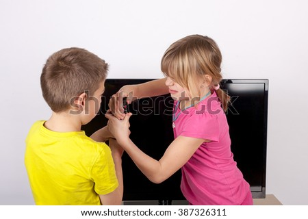Sibling fighting for the remote control in front of the television. - stock photo