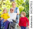Sibling kids, their grandmother and grandfather in wheelchair in summer garden. Happy family spending time together. - stock photo