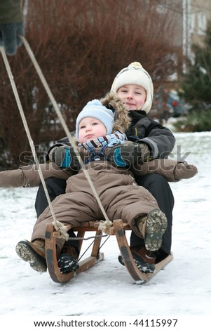 Sibling on sled - stock photo