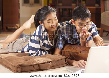 sibling study, boy and girl sibling, playing computer on the floor. - stock photo