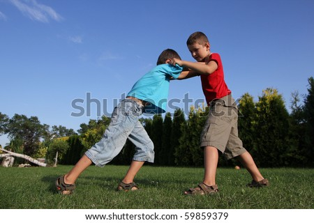 Sibling, two boys, friends boxing. Six and eight old boys  fighting. - stock photo