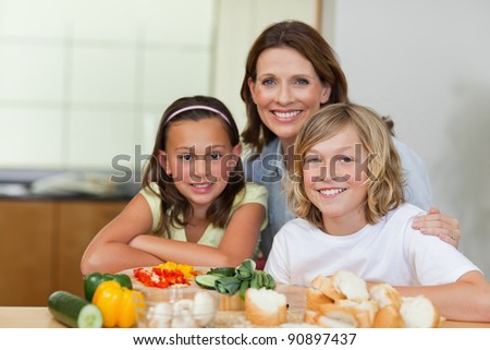 Siblings and mother making sandwiches together - stock photo