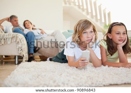 Siblings are bored by tv program - stock photo