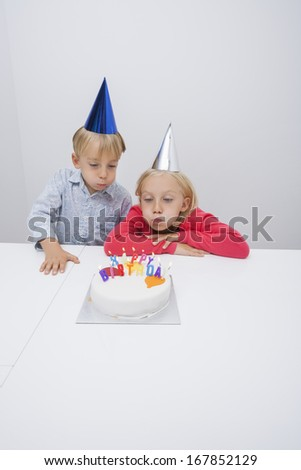 Siblings blowing birthday candles at table in house - stock photo