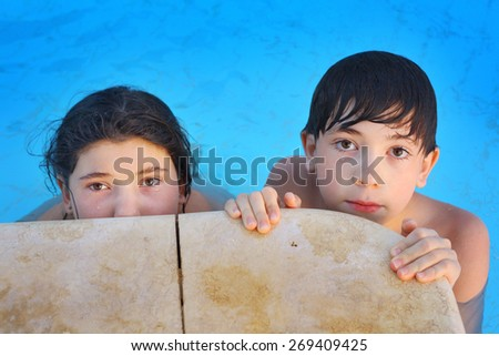 siblings boy and girl play in open air swimming pool at the egyptian sea resort hotel - stock photo