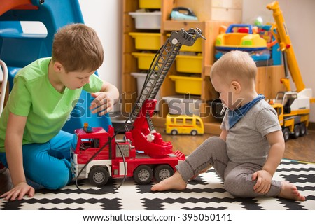 Siblings boys playing with a toy fire truck in kids room. Children playing cars in their room. Leisure activities at home. Playground. indoors. Profession. Fireman. - stock photo