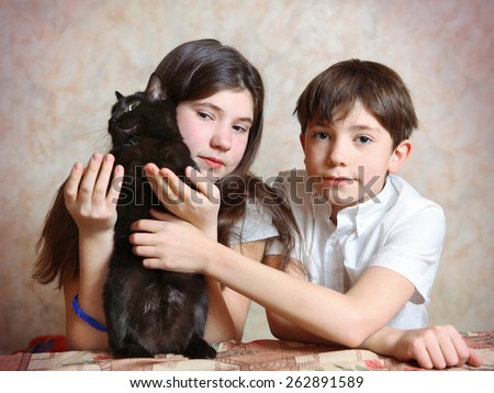 siblings brother and sister cute portrait with black cat - stock photo
