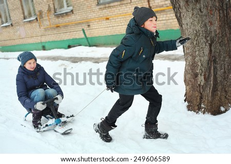 siblings brother and sister ride snow scooter - stock photo