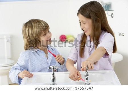 Siblings Brushing Teeth Together at Sink - stock photo