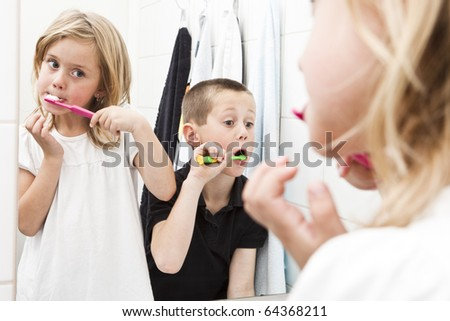 Siblings brushing teeths in the bathroom - stock photo