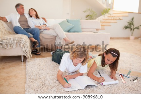 Siblings doing their homework on the floor with parents behind them - stock photo