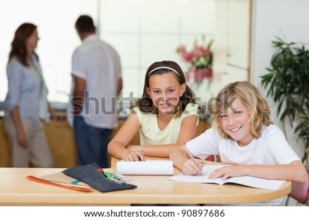 Siblings doing their homework with their parents behind them - stock photo