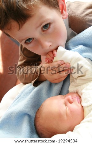 siblings - dreaming newborn baby and 5 years old brother - stock photo
