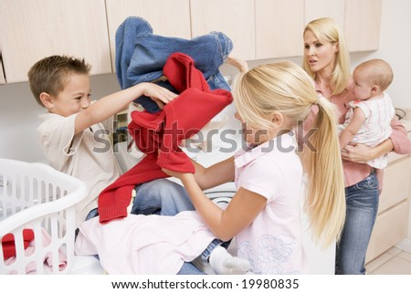 Siblings Fighting While Doing Laundry - stock photo