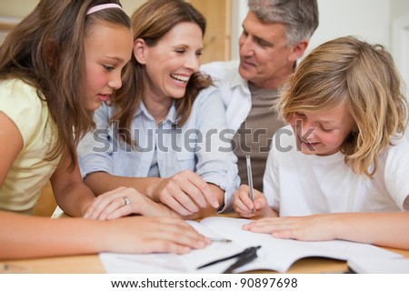 Siblings getting help with homework from their parents