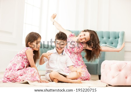 Siblings having fun and using tablet while sitting on the floor - stock photo