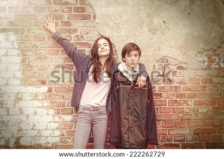 siblings in front of an old grungy brick wall - stock photo