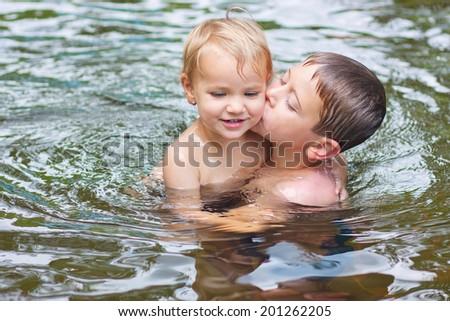 Siblings kissing in the pool - stock photo