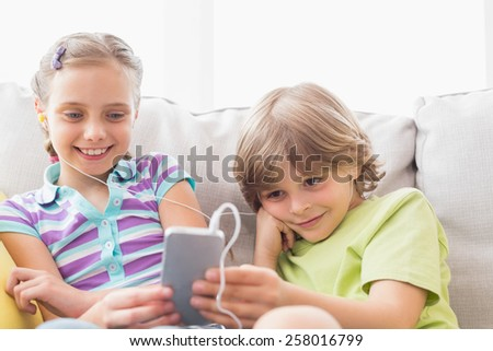 Siblings listening music through mobile phone on sofa at home - stock photo