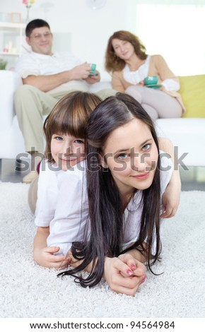 Siblings looking at camera with their parents sitting on sofa at background