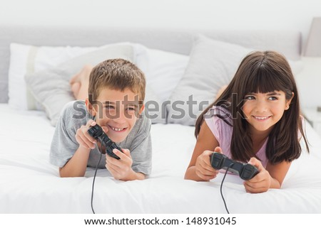 Siblings lying on bed playing video games together at home - stock photo