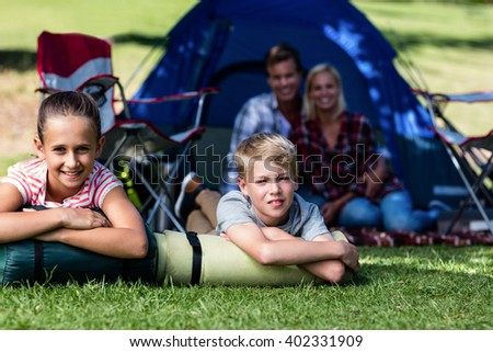 Siblings lying on grass outside the tent and parents sitting in background - stock photo
