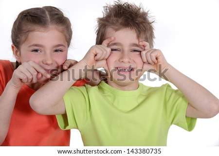 Siblings making funny faces. - stock photo