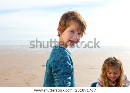 Siblings on the Beach Playing in the Sand - stock photo