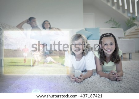 Siblings on the floor watching tv against rugby players tackling during game - stock photo