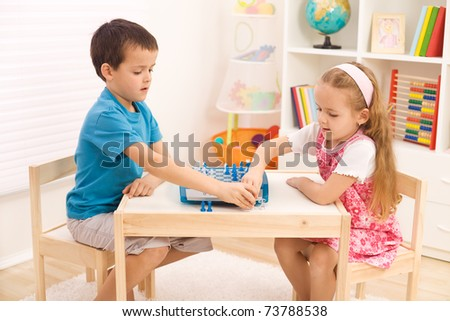 Siblings playing chess in their room sitting at the table - stock photo