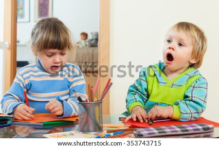 siblings playing with pencils in home - stock photo