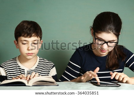 siblings preteen boy read book and teen girl in myopia glasses play tablet pad computer games