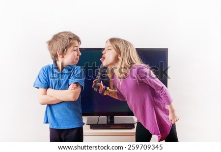 Siblings quarreling over the remote control in front of the television - stock photo