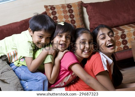 siblings ranging age from eleven to four are having fun together - stock photo