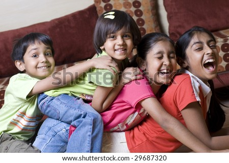 siblings ranging age from eleven to four are having fun together at home - stock photo
