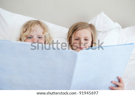 Siblings reading bedtime story together - stock photo