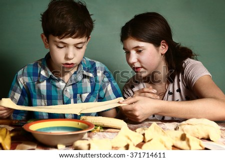 siblings sister teach brother boy how to bake apple pies - stock photo