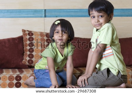siblings sitting in front of each other at home