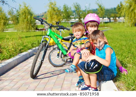 Siblings sitting on grass, their bikes stand behind - stock photo