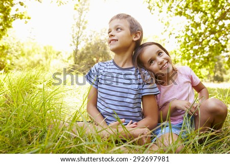Siblings sitting outdoors on a sunny day
