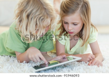 Siblings together on the floor using tablet - stock photo