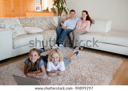 Siblings together with laptop on the floor - stock photo