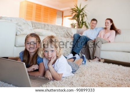 Siblings together with notebook on the floor - stock photo