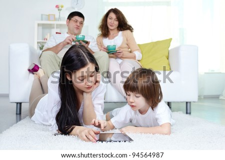Siblings using digital display with their parents sitting on sofa at background